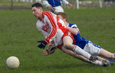 Caoimhín Carty of St. Jarlath's fists the ball away from Michael Connolly of St Colman's