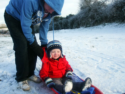 Two boys play with a sled