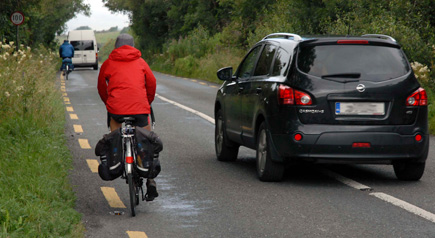 By law, cyclists are supposed to cycle on the left of the road, with walkers on the right. This picture show a vehicle trying to pass cyclists just before a dangerous bend on the N59.