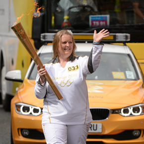 Torchbearer Pamela Lacken, from Ballina is pictured waving to the crowd while carrying the Olympic Flame during the 2012 Olympic Torch Relay through the streets of Dublin last week.