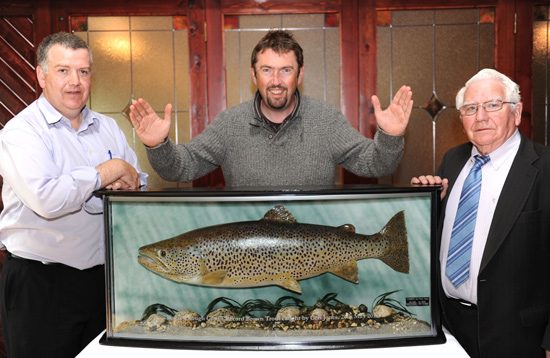 Ceri Jones (centre) is pictured with Tomás Burke (left) and Ciaran Burke of Burke's Bar in Clonbur last Friday evening as they mounted the record-breaking Brown Trout which Ceri caught on Lough Corrib back in May.