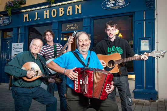 Tom Mulloy (centre) and Pat Mulloy (extreme left) are pictured with Neil Mulloy and Tom McGinty outside Hoban's Bar in Westport.