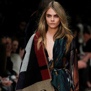 Model Cara Delevinge wearing a monogrammed Burberry Blanket Poncho cape at London Fashion Week