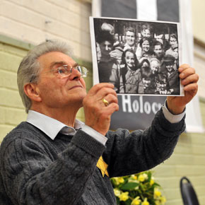 y VIVID Holocaust survivor Tomi Reichental holds up a picture of children who were liberated from a Nazi camp in 1945.